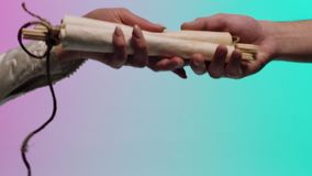 Male hand giving an ancient, rolled manuscript to a woman hand, isolated on green and pink background. Stock. Man stock footage