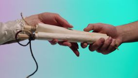 Male hand giving an ancient, rolled manuscript to a woman hand, isolated on green and pink background. Stock. Man stock video footage