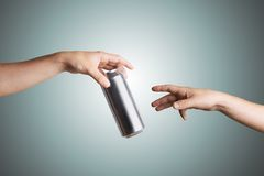 Male hand giving a beer can to another person Stock Photo