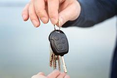 Male hand giving car and house keys to female. Male hand giving a car and house keys to female person, focus on hands Stock Photos
