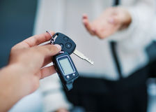 Male hand giving car key to female hand. Stock Images