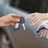 Male hand giving car key to female hand. Stock Image