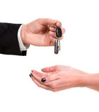 Male hand giving car key to female hand. On a white background Stock Images