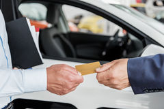 Male hand giving gold card to consultant stock photos