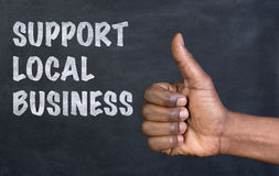 Male hand giving the thumbs up gesture to the phrase Support Local Business Stock Image