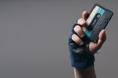 Male hand with glove holding an old music tape. A male hand with glove holding an old music tape royalty free stock photography