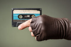 Male hand with glove holding an old music tape. Hand with glove holding an old music tape stock images