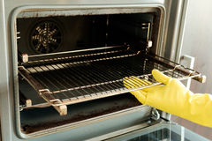 Male hand with gloves cleaning oven royalty free stock photo