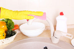 Male hand in gloves with sponge washing faucet. Royalty Free Stock Photos