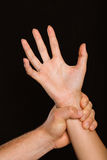 Male hand grabbing female wrist. On black background Royalty Free Stock Image