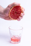 Male hand gripping grapefruit, grapefruit juice on white background Royalty Free Stock Images