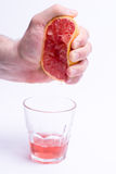 Male hand gripping grapefruit, grapefruit juice on white background Stock Photos