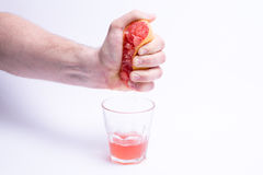 Male hand gripping grapefruit, grapefruit juice on white background Royalty Free Stock Photo