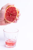 Male hand gripping grapefruit, grapefruit juice on white background Royalty Free Stock Photography