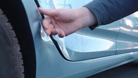 A male hand groping a dent on the door of a wrecked car, checking cracks and paint chips, pressing with a finger, assessing damage