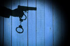 Male Hand with Gun and Handcuffs on Natural Wood Background, XXX Stock Photography