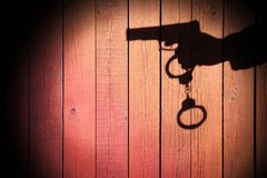 Male Hand with Gun and Handcuffs on Natural Wood Background, XXX Stock Photo