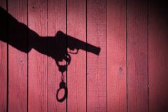 Male Hand with Gun and Handcuffs on Natural Wood Background, XXX Royalty Free Stock Photo