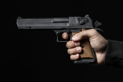 Male hand with gun isolated on black Stock Photo