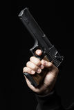 Male hand with gun isolated on black Stock Images