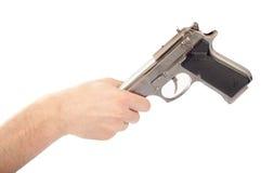 Male hand handing the gun to someone Stock Photo