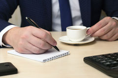 Male hand with the handle and a coffee cup. On a table Stock Image