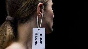Male hand hanging dumb blond label on female ear, social prejudice and sexism. Stock footage stock footage