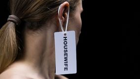 Male hand hanging housewife label on female ear, outdated woman role in society
