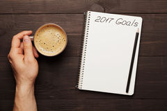Male hand hold cup of coffee and notebook with goals for 2017. Planning and motivation for the new year concept. Top view. Male hand hold cup of coffee and Royalty Free Stock Images