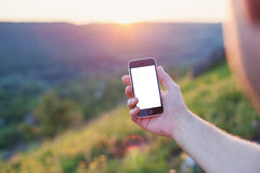 Male hand hold the phone on a background of sunset Royalty Free Stock Photo