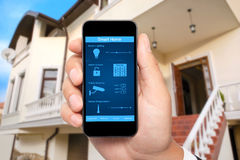 Male hand hold a phone with system smart house on the background. Male hand hold a phone with system smart house on a screen on the background of the house