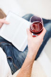 Male hand holdind book and glass of red wine Stock Images