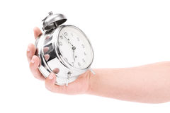 Male hand holding an alarm clock isolated on white background. A close-up shot of a male hand holding an alarm clock isolated on white background Royalty Free Stock Photos