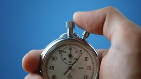 Male hand holding analogue stopwatch on blue color background. Time start with old chronometer man presses start button