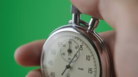 Male hand holding analogue stopwatch on green screen chroma key. Time start with old chronometer man presses start