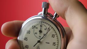 Male hand holding analogue stopwatch on red background. Time start with old chronometer man presses start button in the