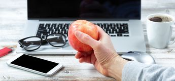Male hand holding apple fruit with workstation technology in background stock images