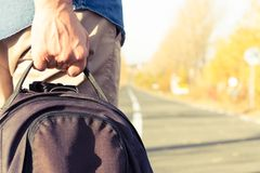 Male hand holding backpack waiting for pickup. On a sunny autumn day on the side of the road Stock Photography