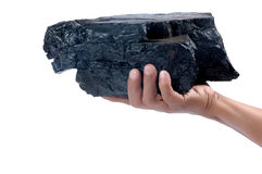 Male hand holding a big lump of coal. Isolated on white background Royalty Free Stock Photos