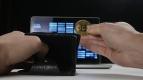 Male hand holding bitcoin and putting it in his wallet. Concept of earning crypto currency. Mining bitcoin.