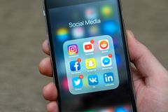 Social media app icons displayed on Apple iPhone, some icons with notifications stock photography