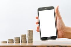 Male hand holding black smart phone and money coin stack Royalty Free Stock Photography