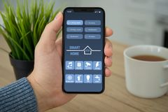 Male hand holding black touch phone with app smart home Stock Photo