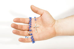Male hand holding blue beads rosary Stock Images