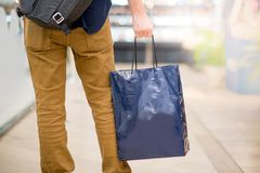 Male hand holding blue shopping bag in department store. Closeup of male hand holding blue shopping bag in department store. Urban lifestyle in shopping mall Royalty Free Stock Image