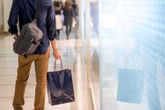 Male hand holding blue shopping bag in department store. Closeup of male hand holding blue shopping bag in department store. Urban lifestyle in shopping mall Stock Images