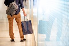 Male hand holding blue shopping bag in department store. Closeup of male hand holding blue shopping bag in department store. Urban lifestyle in shopping mall Stock Photos
