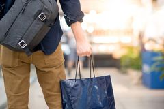 Male hand holding blue shopping bag in department store. Closeup of male hand holding blue shopping bag in department store. Urban lifestyle in shopping mall Royalty Free Stock Photos