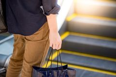 Male hand holding blue shopping bag in department store. Male hand holding blue shopping bag near escalator in department store. urban lifestyle in shopping mall Royalty Free Stock Images