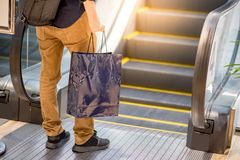 Male hand holding blue shopping bag in department store. Male hand holding blue shopping bag near escalator in department store. urban lifestyle in shopping mall Royalty Free Stock Photo